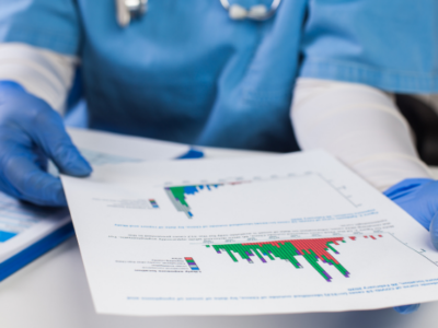 physician with blue gloves looking at a healthcare report with colorful graphs