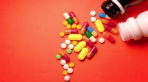 Various colored pills spilling out of bottles on red background