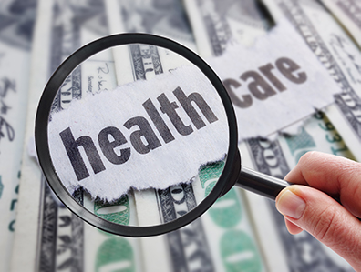 Magnifying glass inspecting the words health care stacked on top of $100 bills